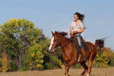 Girl riding  horse  on autumn field