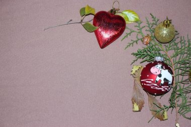 Festive New Year's composition of pine needles and Christmas tree decorations in the form of a heart and balls with the symbol of the year bull on a brown background. Negative space