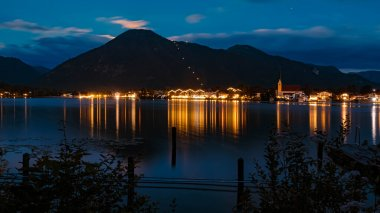 Long exposure night shot with Rottach-Egern and reflections in the background at the famous Tegernsee, Bavaria, Germany