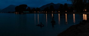 High resolution stitched panorama of a long exposure night shot with reflections at the famous Tegernsee, Bad Wiessee, Bavaria, Germany