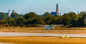 Schöner Herbst- oder indischer Sommerblick mit einem startenden Flugzeug vor einer Kirche im Hintergrund am Flughafen Straubing, Bayern, Deutschland