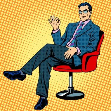 Businessman sitting in an armchair gesture okay
