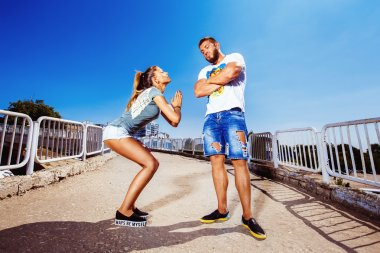 Young attractive girl is asking her man for forgiving making common gesture at summer bright background.