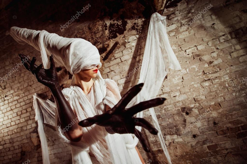 Closeup portrait of blind insane creature in cocoon stretching black hands towards watche at bricks wall background. Concept of horror movie.