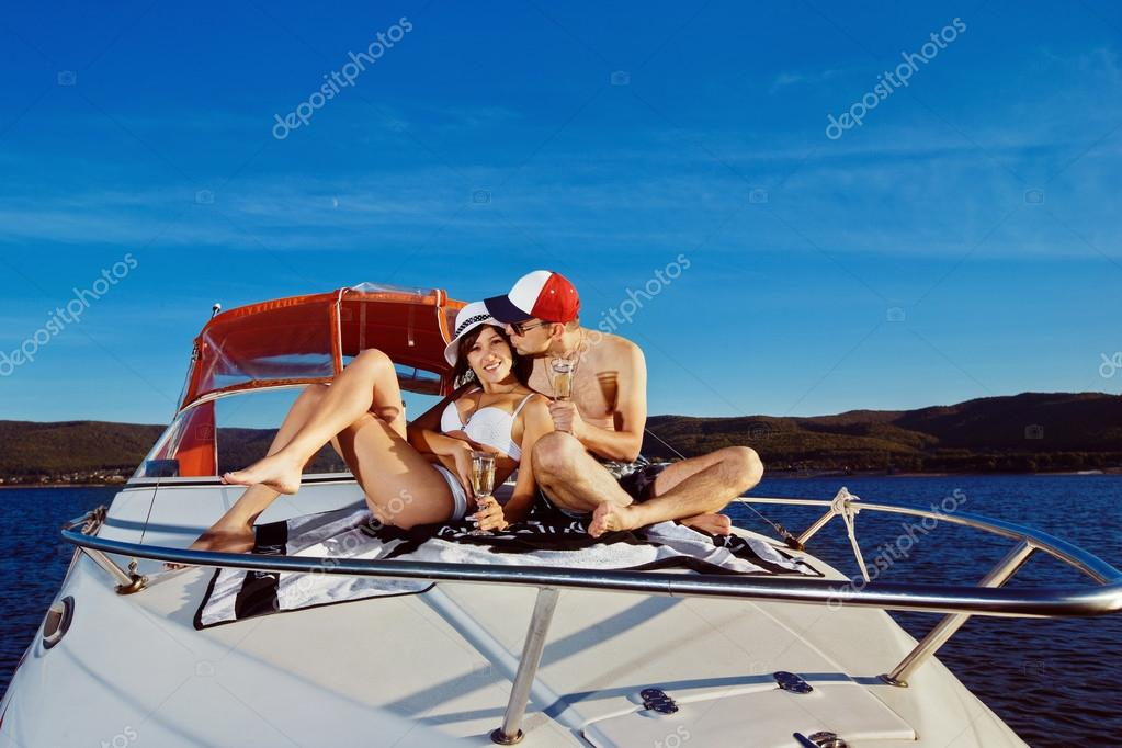 Beautiful young happy couple is sitting on boat and drinking champagne at blue background.