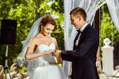 Closeup portrait of elegant wedding ceremony. Groom is putting ring on bride's finger at green outdoors background.
