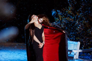 Beautiful female vampire in long pallium is biting her victim at blue light cold winter evening background.