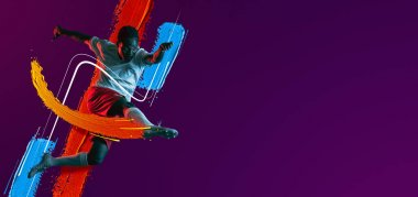 African soccer football player jumping isolated on purple neon background. Flyer. Vibrant colors