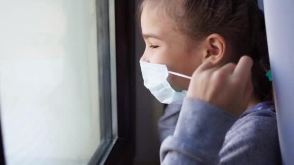 glückliches Teenie-Mädchen zieht Schutzmaske ab, schaut aus dem Fenster nach draußen.