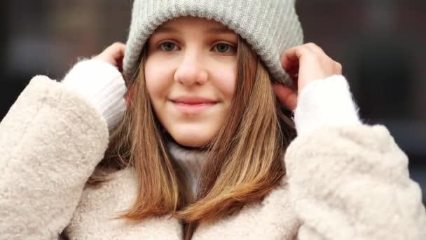 Krásná dospívající dívka drží ruce na teplé pletený šedý klobouk.