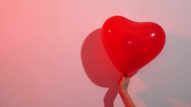 Srdce ve tvaru červeného balónku v ruce proti bílé stěně v barevném světle