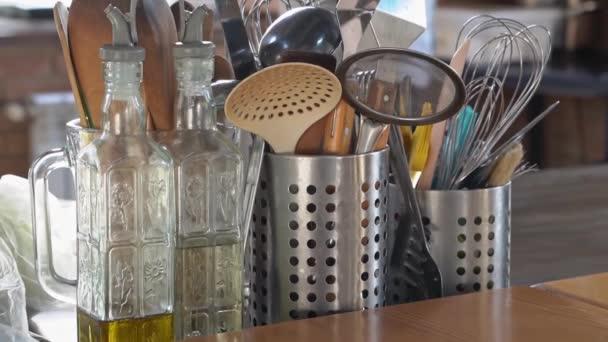 kuchyňský stolek. Kovové stojany s příbory, skleněné láhve s olivovým olejem a octem