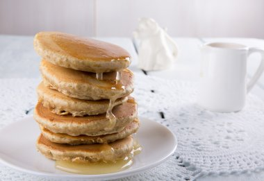 Stack of homemade whole wheat pancakes with a honey
