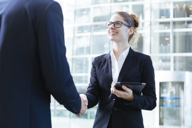 Two young business people shaking hands