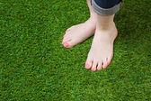 Nő lába injeans állt a zöld fű