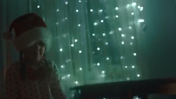 Familie schmückt ihr Zuhause für die Weihnachtsfeiertage - glückliche Kinder haben Spaß beim Spielen mit den Lichtern und Dekorationen und Umarmungen. Frohe Weihnachten und frohe Feiertage. Glückliche Familienzeit. 4K-Video