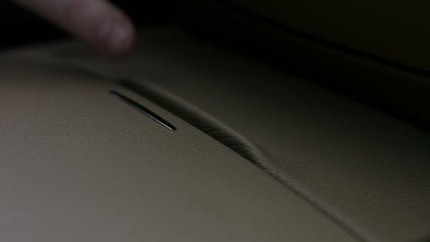 Im Innenraum eines Luxusautos. Ein Mann öffnet den Becherhalter mit der Hand. 4K-Video