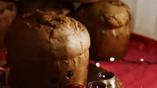 Tradiční italské pečivo k Vánocům se sušeným ovocem. Sladký sváteční chléb Panettone z Milána. Krásná vánoční atmosféra s ozdobami, svíčkami a světly. Vysoce kvalitní 4K záběry