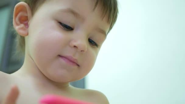 Liebenswerter kleiner Sohn mit Smartphone schaut lustige Videos