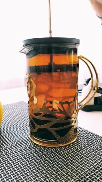 Man pressed French press with tea on the table