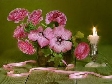 Pink roses in a basket and a candle.