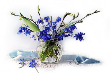 Blue flowers in spring water in a glass vase.