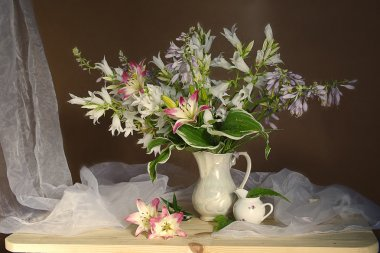 Still life with white flowers:Campanula and lilies in a vase .