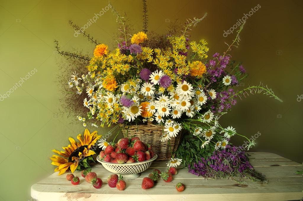 Still life with berries and flowers . Red , ripe strawberries and a bouquet of wildflowers and sunflowers .