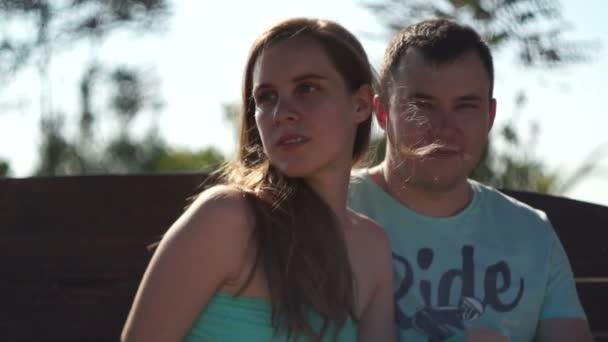 Fiatal pár ül a padon. Romantikus hangulat
