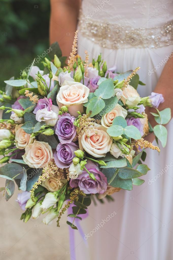 Photo of happy bride holding a wedding bouquet
