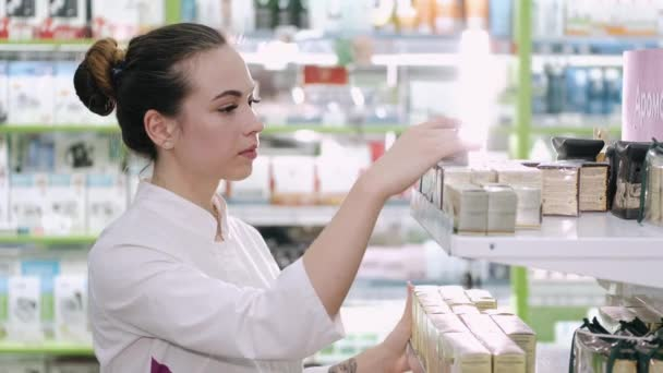 A female pharmacist is looking at some products on the shelf