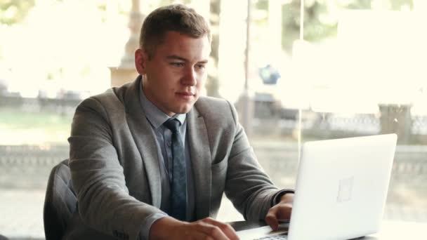 Obchodní muž v obleku pomocí notebooku v kavárně