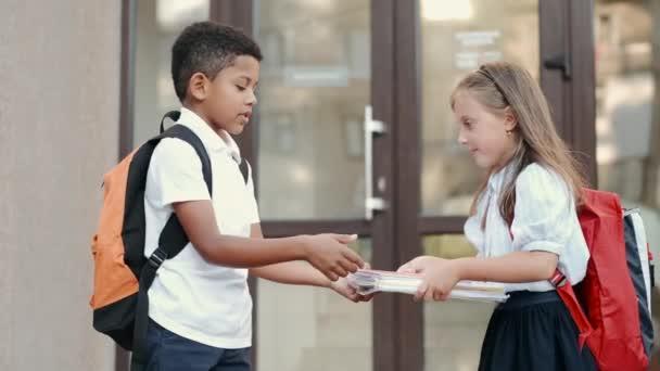 Dvě školačky s batohy, které si u školy vyměňují knížky