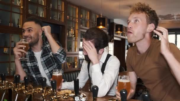 Three happy young men in casual wear watching football while sitting in bar together