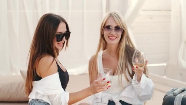 Young pretty women with cocktails and suitcases sitting at lounge zone