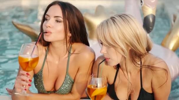 Two sexy young women on deck chairs holding fruits