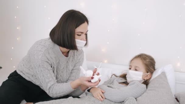 Hübsche Frau und Tochter in Masken heilen zu Hause