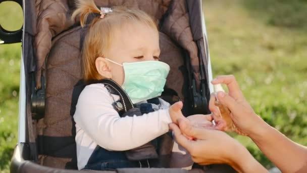 Frau desinfiziert Hände ihrer Töchter im Freien