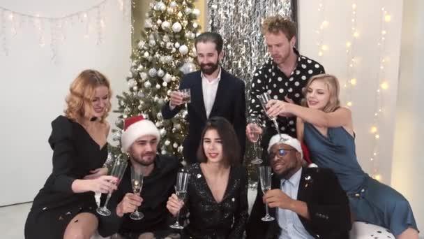 Fiatal baráti társaság pezsgőzik otthon a kanapén szilveszterkor.