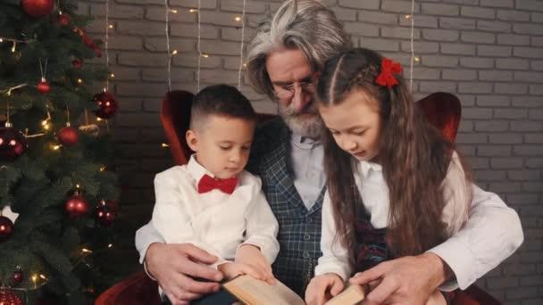 Großvater und Kinder lesen an Heiligabend ein Buch