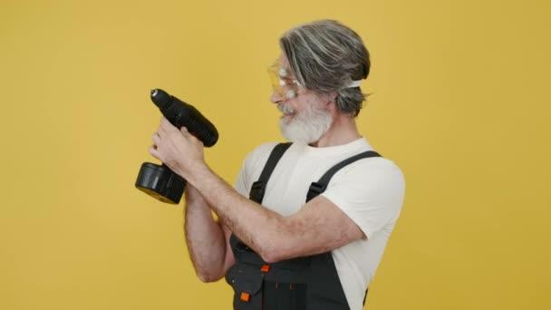 Stavební dělník v ochranných sklech s perforátorem izolovaným na žlutém pozadí