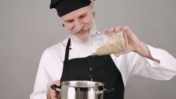 Středního věku kuchař nalévání obilovin na šedém pozadí