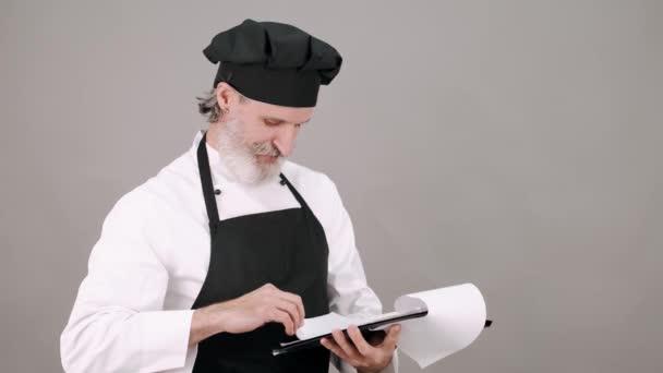Porträt eines älteren männlichen Kochs, der mit Notizblock entscheidet, was er kochen soll