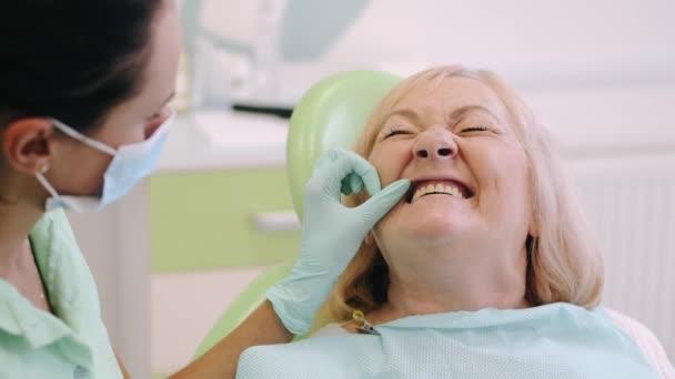 Žena zubní lékař vyšetření starší ženy zuby v kanceláři