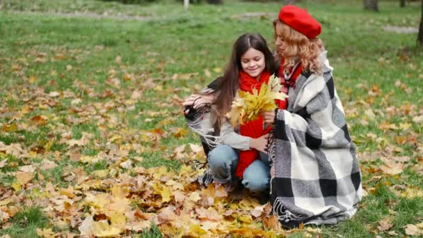 Mother And Her Daughter Playing With Fallling Leaves In Autumn Park