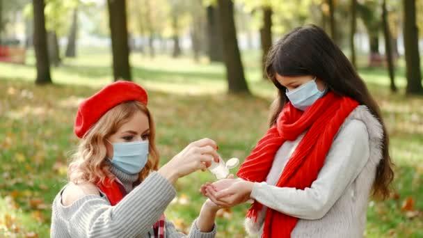 Mutter und Tochter desinfizieren Hände im Park