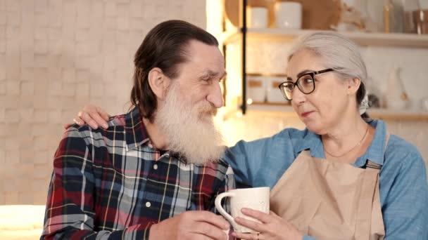 Pečující starší žena dává čaj staršímu muži v domácí kuchyni