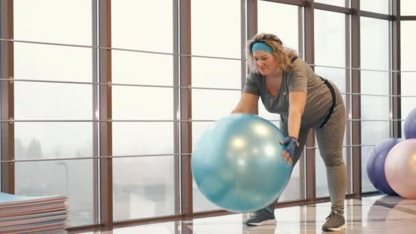 Curvy dívka cvičení s fitness míč v tělocvičně