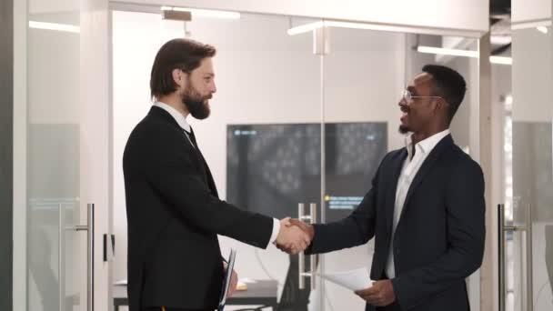 Dva usměvaví obchodníci si potřásají rukama, když stojí v kanceláři