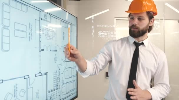 Confident man enginner stand near digital monitor and presenting the project